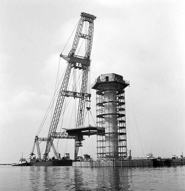 28 augustus 1973: met een drijvende bok wordt het helikopterplatform op het zuidelijke havenlicht gehesen.